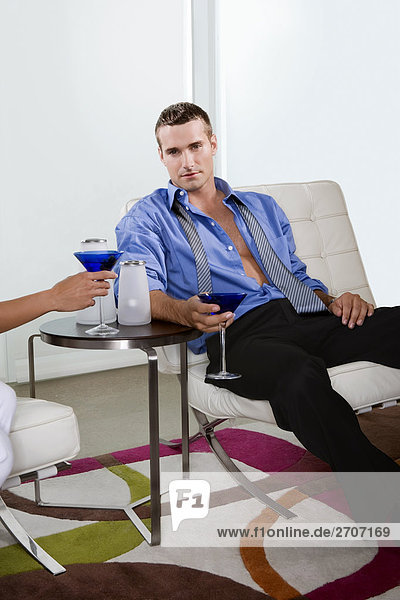 Young man sitting on a chair and holding a glass of cocktail