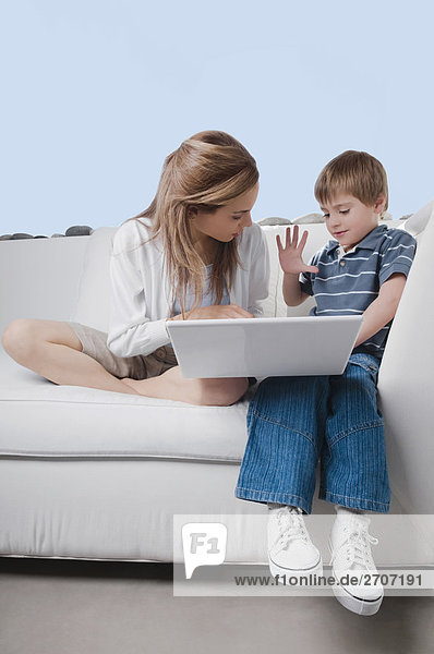 Mid adult woman working on a laptop with her son