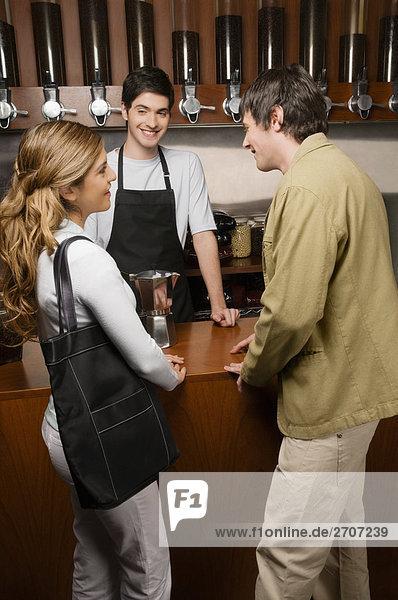 junges Paar mit einem Cafe Besitzer stehen an einem Schalter einen Coffee-shop