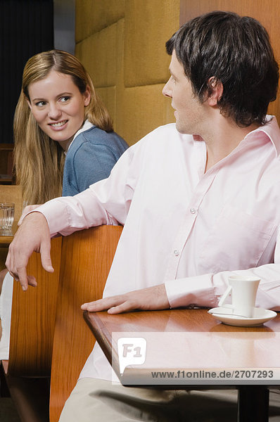 Junger Mann im Gespräch mit einer jungen Frau in einem Café