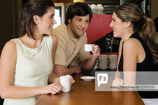 Kellnerin im Gespräch mit zwei Kunden an einem Schalter