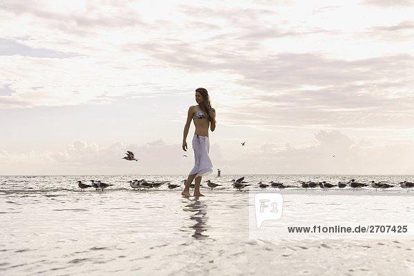 Junge Frau zu Fuß am Strand