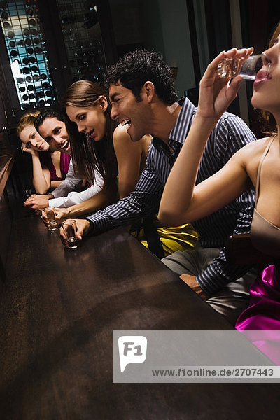Fünf Freunde sitzen in einer Bar zu begegnen und trinken Whiskey