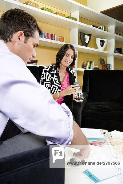 Mitte erwachsen Frau sitzend mit einem mittleren erwachsenen Mann und Text-messaging