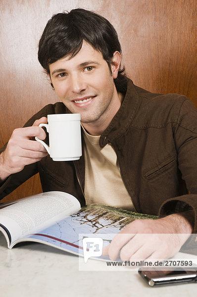 Junger Mann trinkt Kaffee in einem Café und lächelnd