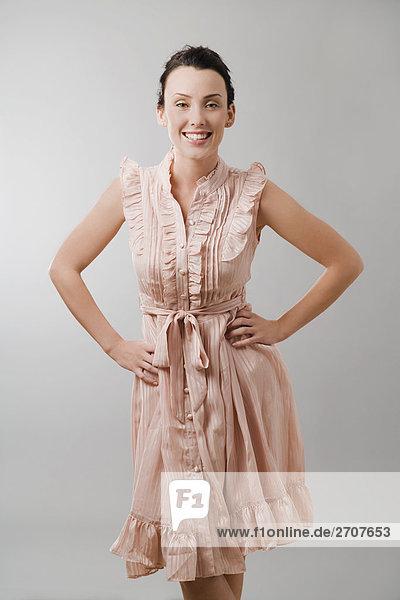 Portrait einer jungen Frau mit Arms akimbo und lächelnd ständigen