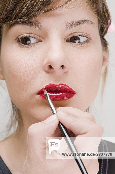 Nahaufnahme einer jungen Frau Anwendung Lippenstift