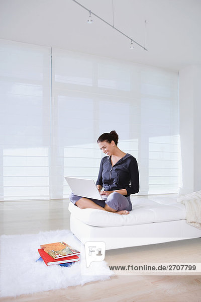 Frau sitzen auf dem Bett und benutze ein laptop