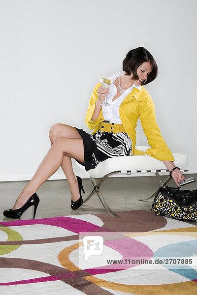 Frau sitzen auf einem Stuhl und Blick auf einem Mobiltelefon