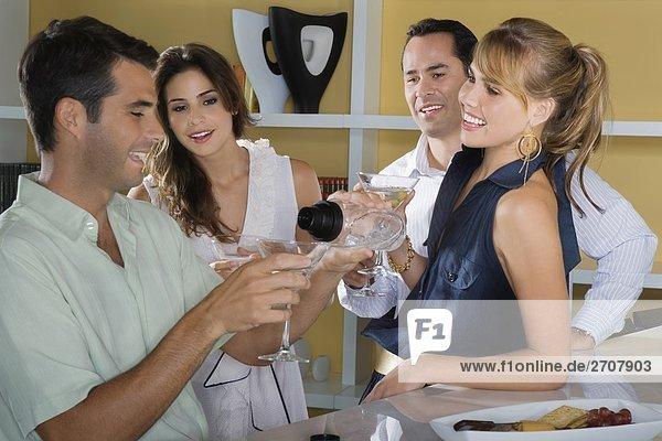 Vier Freunde mit Cocktail feiern