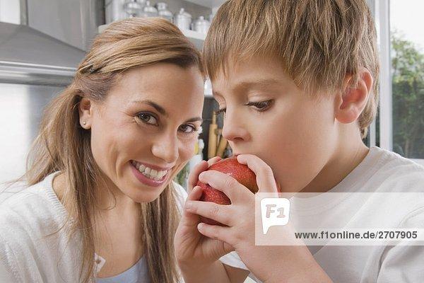 Boy Essen einen Apfel und seine Mutter lächelnd