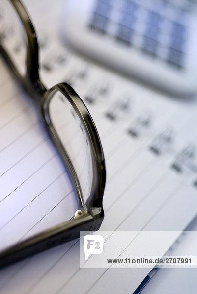 Nahaufnahme Brille auf ein Spiralblock
