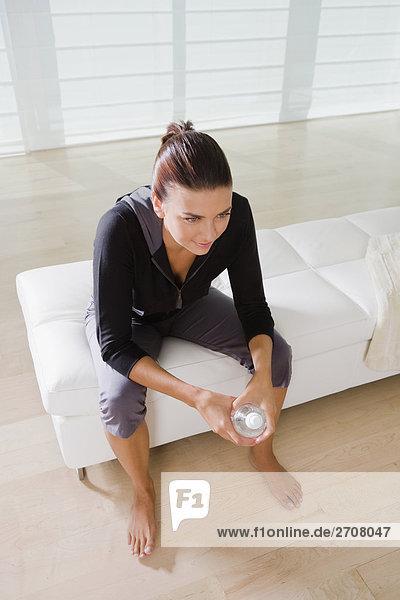 Erhöhte Ansicht einer jungen Frau sitzen auf dem Bett und hält eine Flasche Wasser