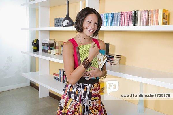 Junge Frau hält Bücher und lächelnd