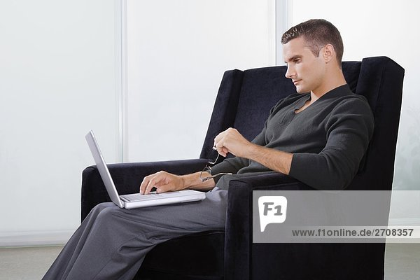 Side profile of a young man sitting in an armchair and working on a laptop