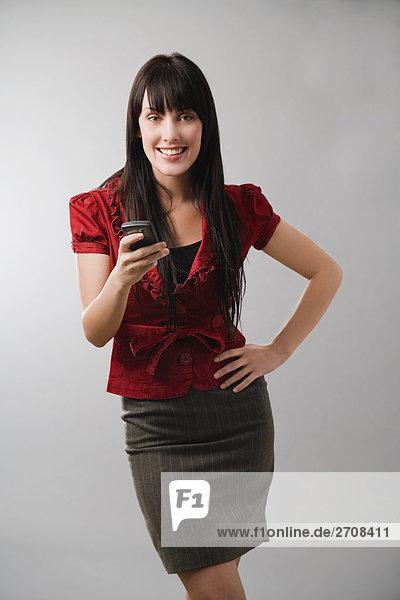 Portrait einer jungen Frau mit einem Mobiltelefon und lächelnd