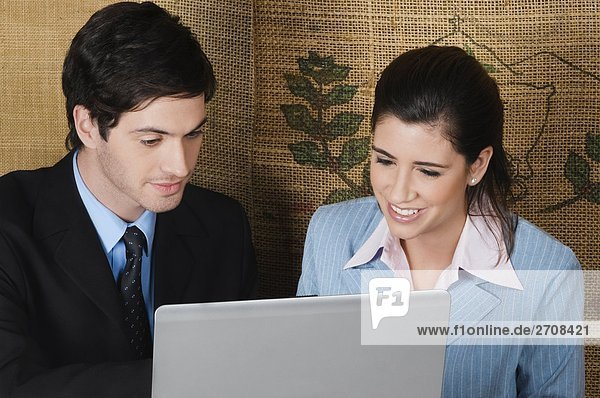 Businesswoman and a businessman using a laptop in a cafe