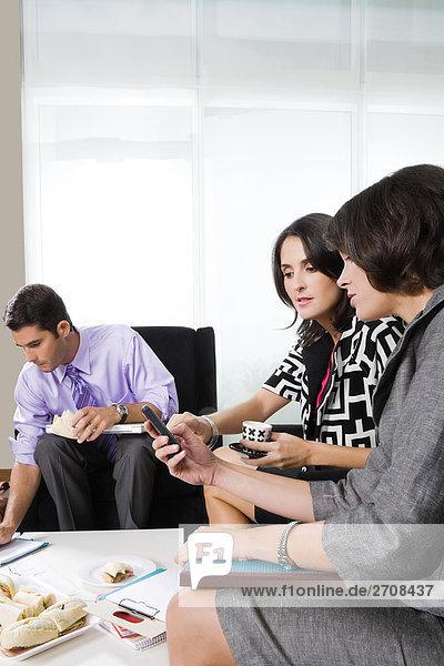 Zwei Geschäftsfrauen Blick auf einem Mobiltelefon