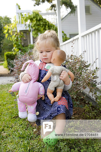 Baby girl holding toys and walking in a lawn
