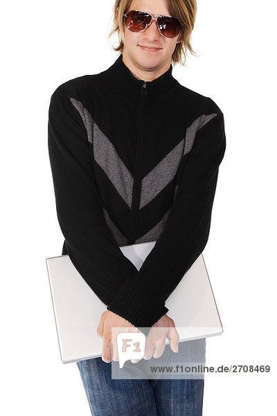 Junger Mann hält einen Laptop und lächelnd