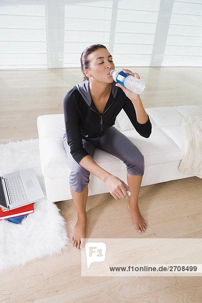 Junge Frau sitzen auf dem Bett und Trinkwasser