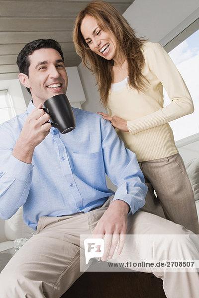 Mitte Erwachsenen Mann  eine Kaffeetasse und eine Mitte erwachsen frau neben ihm lachend hält