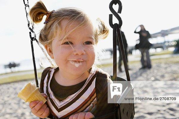 Nahaufnahme ein Babymädchen sitzen auf eine Kette Swing Fahrt und Essen ein Eis Nahaufnahme ein Babymädchen sitzen auf eine Kette Swing Fahrt und Essen ein Eis