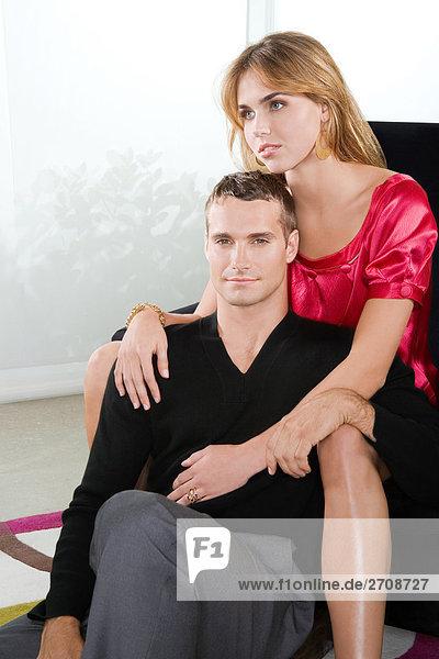 Portrait einer jungen Frau umarmen einen jungen Mann von hinten