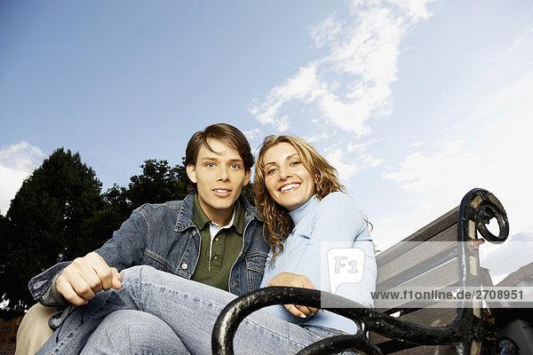 Porträt eines jungen Paares sitzen auf einer Bank
