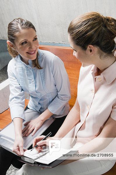 Zwei Geschäftsfrauen auf einer Bank sitzen und lächelnd