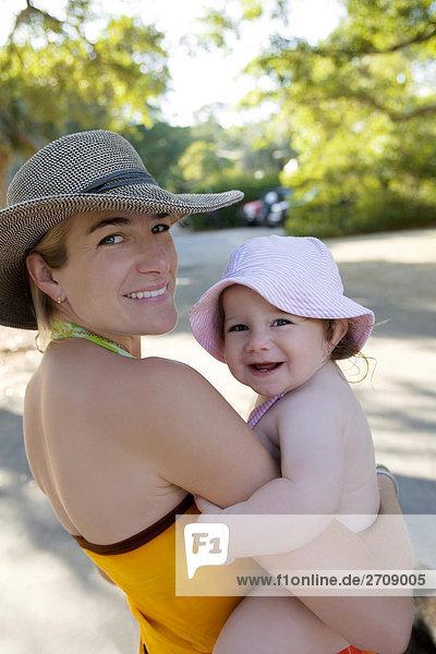 Portrait einer Mitte erwachsen frau tragen ihr Babymädchen und lächelnd