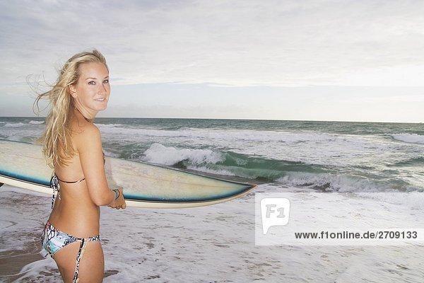 stehend junge Frau junge Frauen Portrait Strand Surfboard
