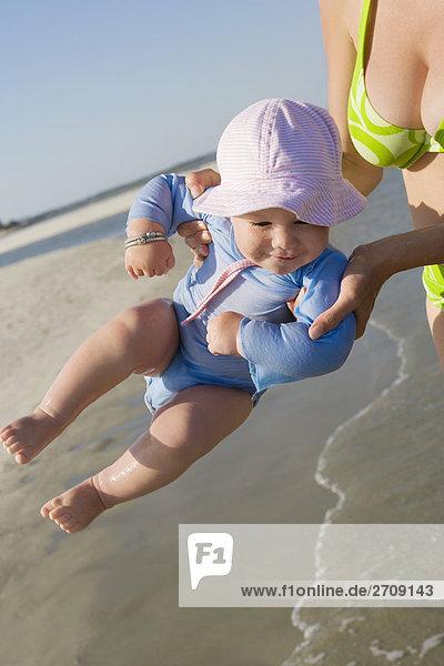 Mitte Schnittansicht einer Frau halten ihr Baby in Luft