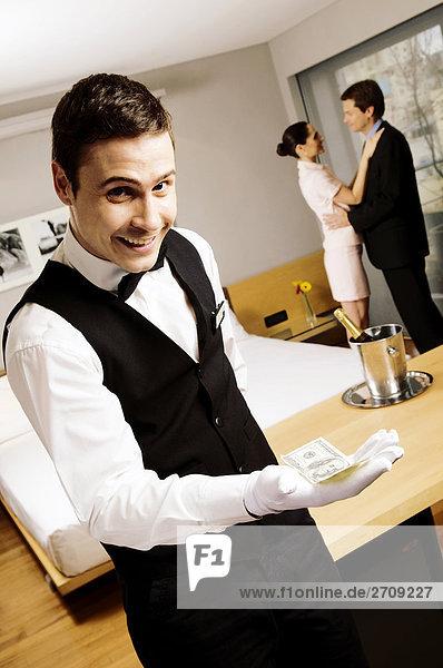 Porträt von einem Kellner hält us-Dollar-Geldschein und lächelnd