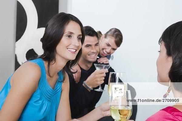 Vier Freunde feiern mit Wein und cocktail
