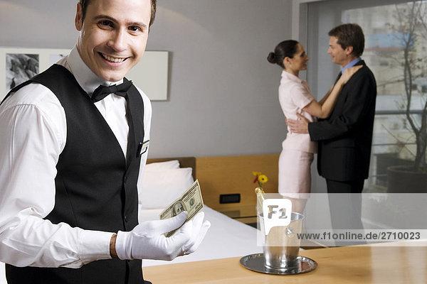Der Kellner hält US-Papier Währung und lächelnd portrait
