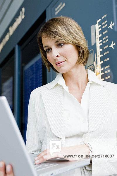 Frau hält einen Laptop hoch und arbeitet