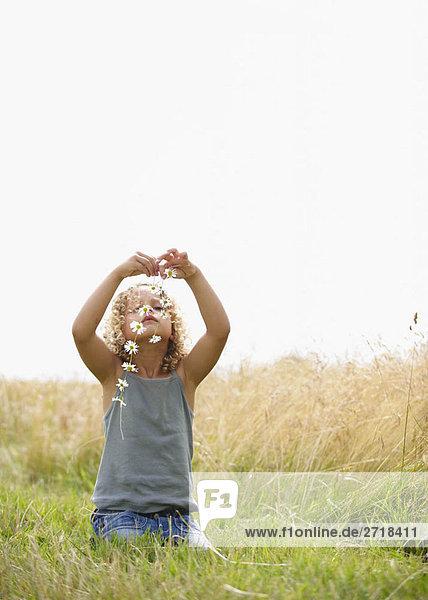 Junges Mädchen macht eine Gänseblümchenkette im Feld