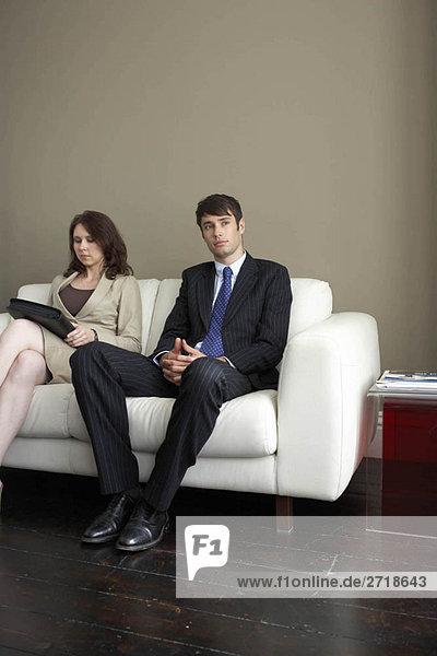 Geschäftsmann und Frau auf dem Sofa sitzend