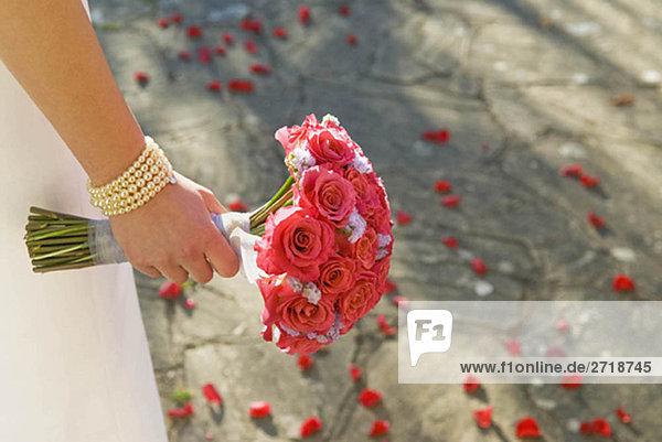 Eine Braut  die einen Rosenstrauß hält.