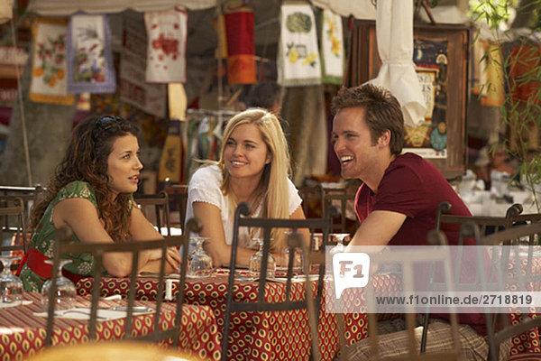Freunde sprechen im französischen Marktcafé