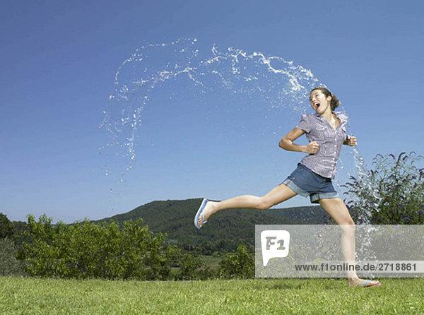 Mädchen läuft durch den Wasserbogen