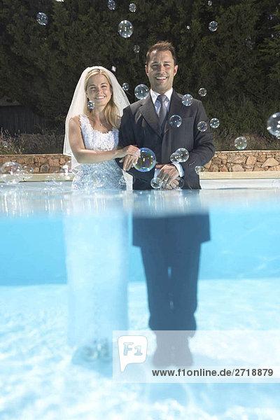Braut und Bräutigam im Pool mit Seifenblasen