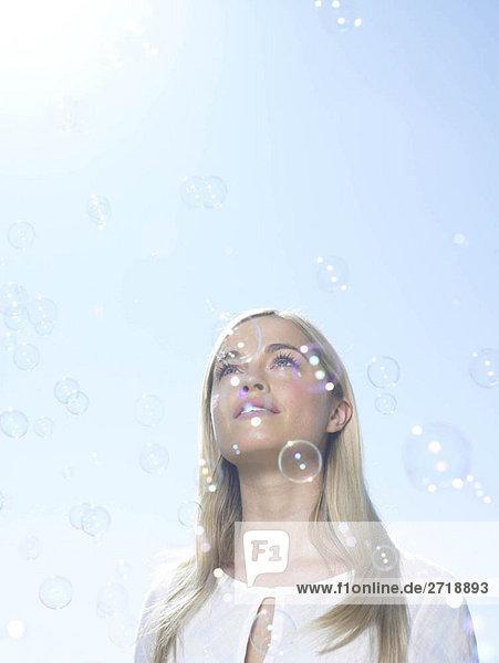 Mädchen schaut in den Himmel mit Blasen