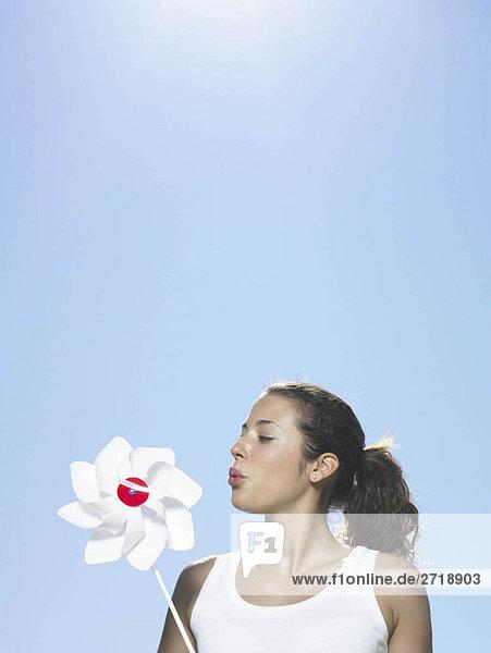 Mädchen bläst Windmühle in der Sonne