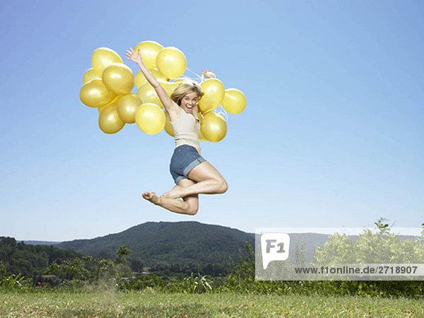 Mädchenspringen mit Luftballons