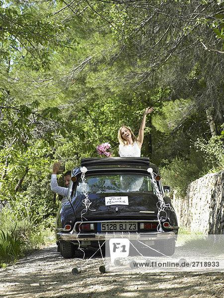 Braut und Bräutigam winken aus dem Hochzeitsauto