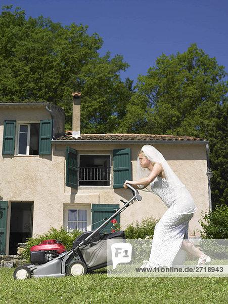 Braut beim Rasenmähen