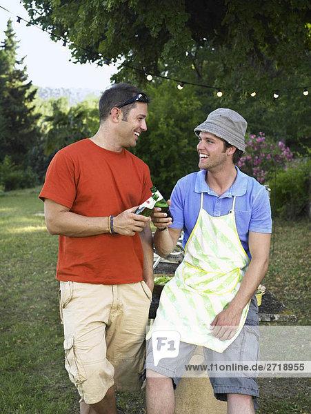 Zwei Männer stoßen beim Grillen an
