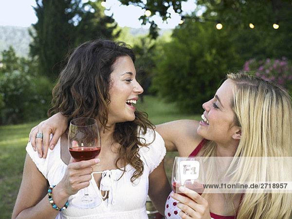 Zwei Frauen lachen beim Grillen